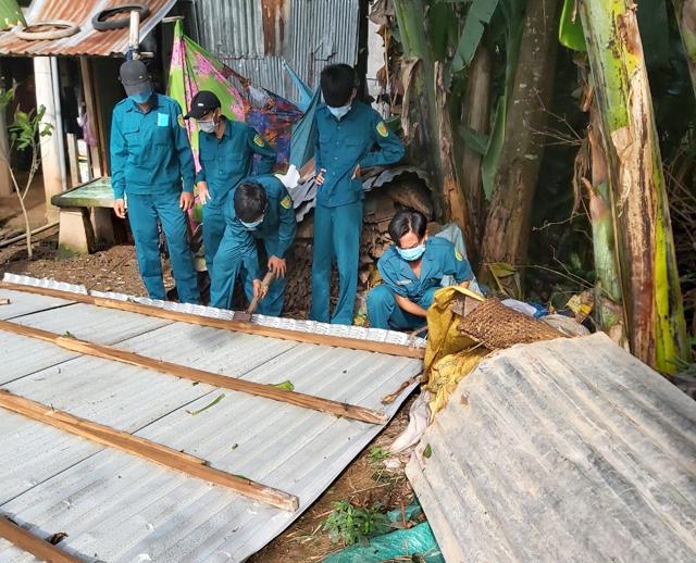 Lực lượng dân quân tự vệ giúp người dân sửa chữa nhà