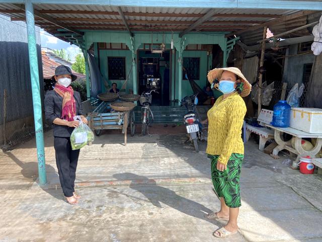 Chị Nguyễn Thị Chi (bên trái) mang những phần nhu yếu phẩm trao tận tay cho hộ nghèo tại xã Phú Thuận A